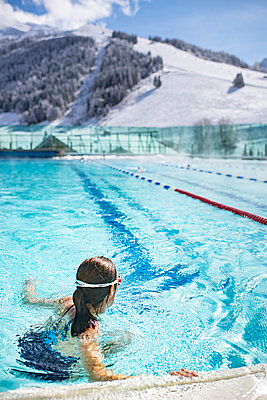 France, La Clusaz, Woman in a swimming pool in winter in the mountains - p1007m2216597 by Tilby Vattard
