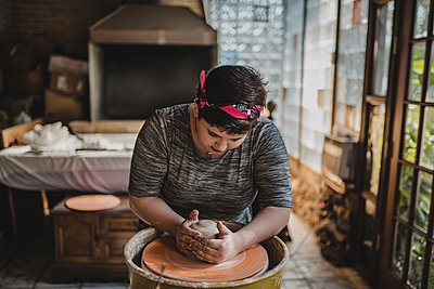 Female craftsperson making clay pot at pottery - p1166m1512988 by Cavan Images