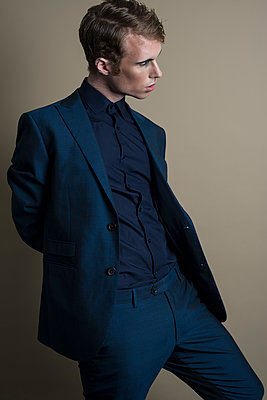 Young man in blue suit, wearing makeup, standing in a contorted position. - p1433m1563447 by Wolf Kettler