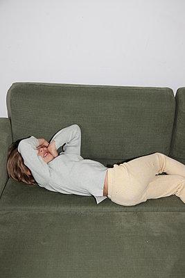 Mädchen liegt auf dem Sofa - p1514m2275712 von geraldinehaas