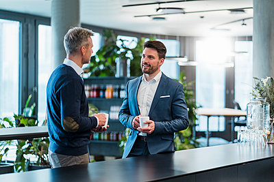 Business people talking while having coffee in office cafe - p300m2274267 by Daniel Ingold