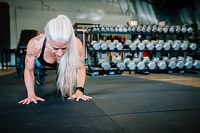 Caucasian woman doing push-up in gymnasium - p555m1303185 by Inti St Clair photography