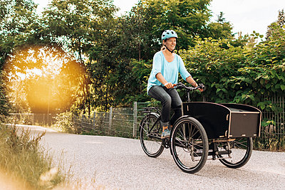 Young woman rides a cargo e-bike - p608m2192840 by Jens Nieth