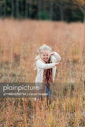 Little girl running through a field of grass taller than herself - p1166m2292794 by Cavan Images