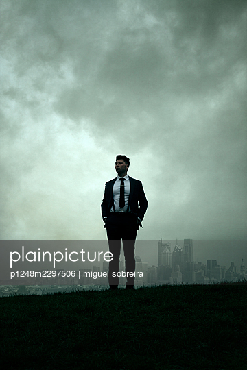 Man in Suit standing on a hill in the background a city - p1248m2297506 by miguel sobreira