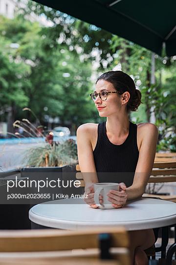 Young businesswoman sitting in coffee shop, taking a break, drinking tea - p300m2023655 von Kike Arnaiz