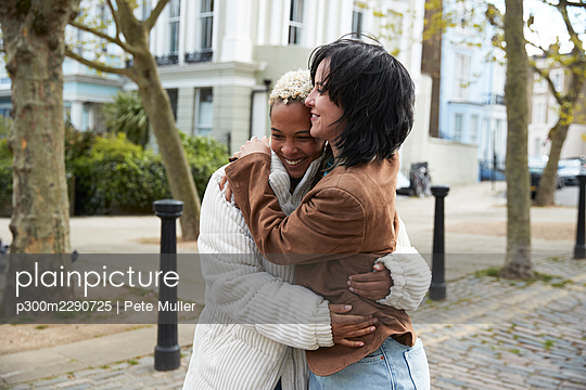 Happy lesbian couple hugging each other standing on footpath - p300m2290725 by Pete Muller