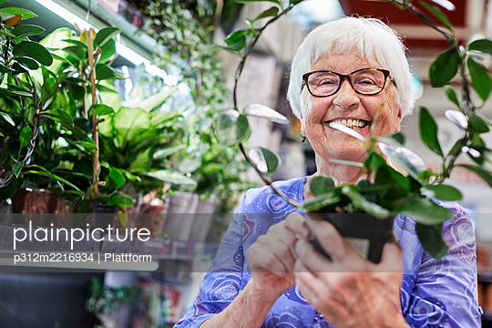 Woman holding potted plants in shop - p312m2216934 by Plattform