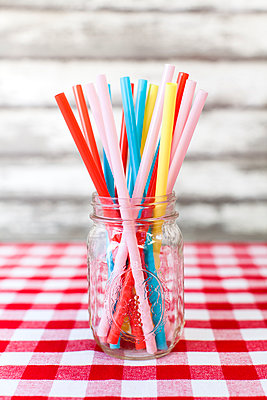 Multi colored drinking straws in glass jar on tablecloth - p1094m1015334 by Patrick Strattner