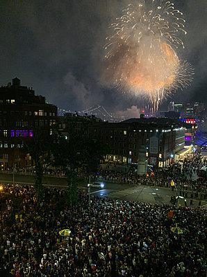 Crowd watching fireworks near Brooklyn Bridge - p1166m2153676 by Cavan Images