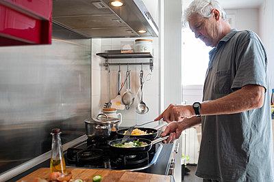 Senior man preparing food in frying pans in his kitchen - p300m2143353 by VITTA GALLERY