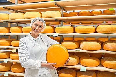 Cheese factory, smiling female worker holding cheese wheel - p300m2199090 by Zeljko Dangubic