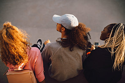 Rear view of friends sitting at skateboard park - p426m2072348 by Maskot