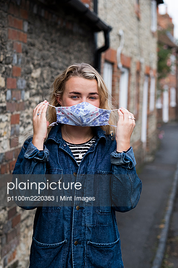 Young blond woman standing outdoors, putting on face mask. - p1100m2220383 by Mint Images