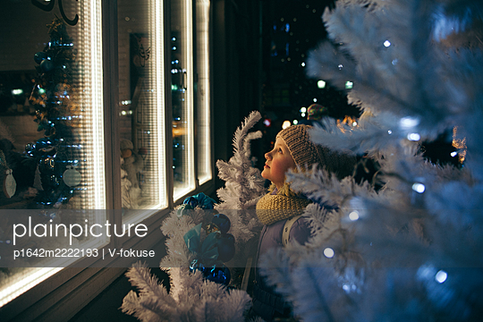 Girl looks out of the window at Christmas time - p1642m2222193 by V-fokuse