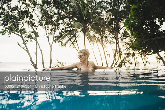 Thailand, Phuket, Naithon Beach, Frau in Infinity Pool im Sonnenuntergang - p300m2166354 von Christophe Papke