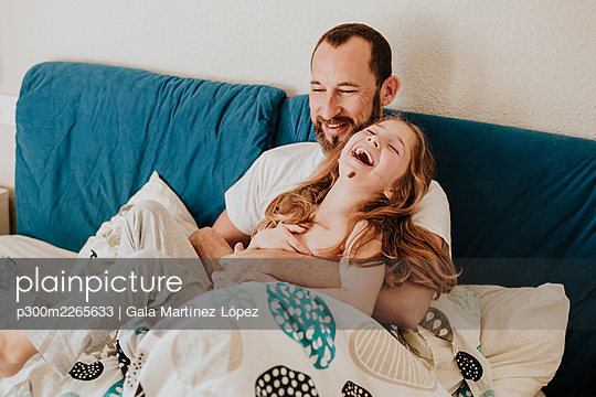 Daughter laughing with father while sitting on bed - p300m2265633 by Gala Martínez López