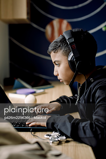 Pre-adolescent boy playing game on laptop in bedroom - p426m2296366 by Maskot
