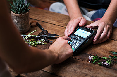 Cropped image of customer paying with credit card in flower shop - p1166m1182705 by Cavan Images