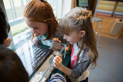 Curious girls watching exhibit display in science center - p1192m1194214 by Hero Images