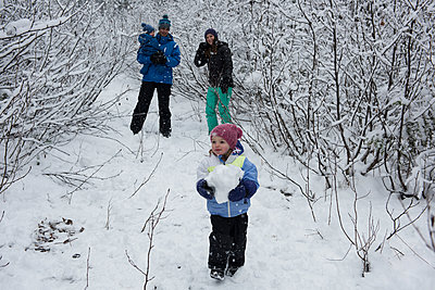 Girl holding snowball with family in background - p1315m1421988 by Wavebreak