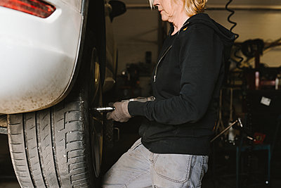 Female mechanic repairing car - p312m2208185 by Stina Gränfors