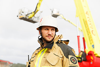 Sweden, Sodermanland, Portrait of young fire-fighter against fire engine - p352m1126953f by Christian Ferm