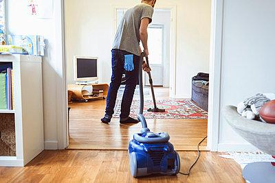 Rear view of man vacuuming carpet - p426m1017962f by Maskot