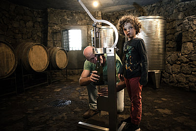 Boy with winemaker corking wine bottle in cellar - p429m1227175 by heshphoto