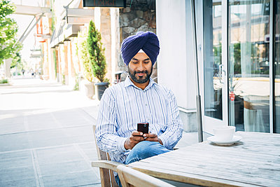 Man wearing turban texting on cell phone at cafe - p555m1304504 by Inti St Clair photography