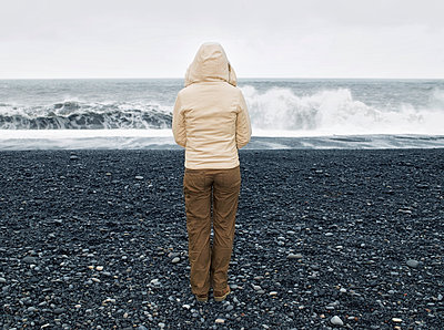 Caucasian woman admiring ocean waves on rocky beach - p555m1410573 by Dave and Les Jacobs