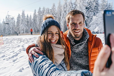 Young couple in winter clothing takes a selfie - p586m2005120 by Kniel Synnatzschke