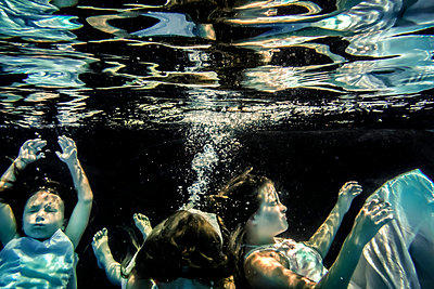 Children floating underwater - p1019m1461894 by Stephen Carroll