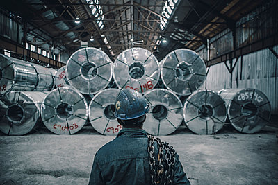 Rear view of male worker carrying chain standing in front of rolled up steel sheets at factory - p1166m1416233 by Cavan Images