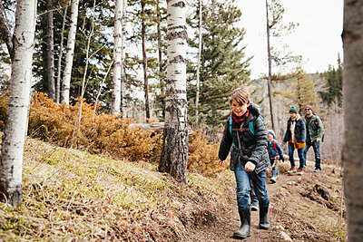 Carefree boy hiking with family in woods - p1192m2094185 by Hero Images
