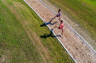 Aerial view of female joggers on woodchip trail - p300m2004677 by Stefan Schurr