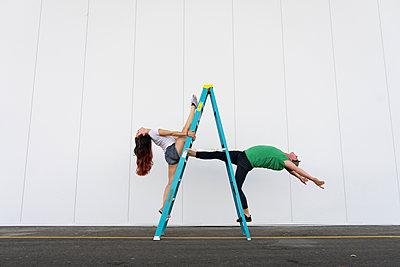 Two acrobats doing tricks on a ladder - p300m2012349 von VITTA GALLERY