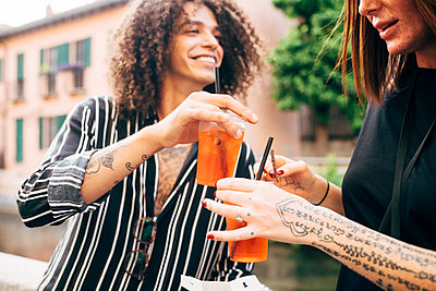 Close-up of happy couple toasting drinks while having fun in city - p300m2206890 by Eugenio Marongiu