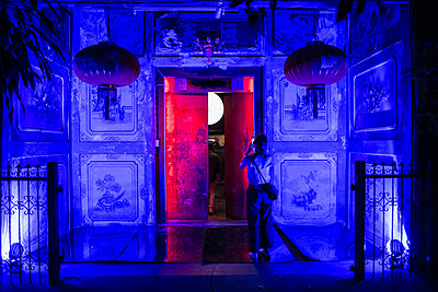 Woman taking photograph of house in lit up alley, Chinatown, Bangkok, Thailand - p429m1561631 by Henn Photography