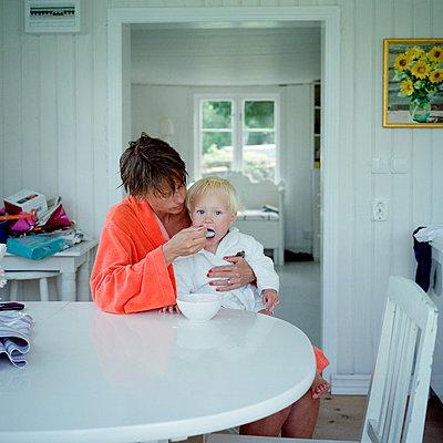 Mother feeding boy - p528m1075501f by Johan Willner