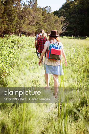 USA, New York, Young people hiking across grassy meadow