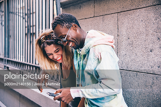 Laughing couple using cell phone outdoors - p300m2140156 by Jesús Martinez
