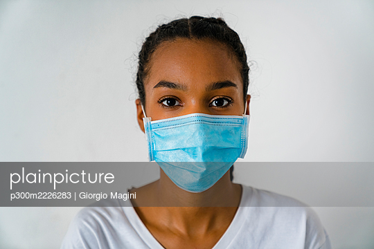 Teenage girl wearing protective face mask standing against wall during covid-19 - p300m2226283 by Giorgio Magini