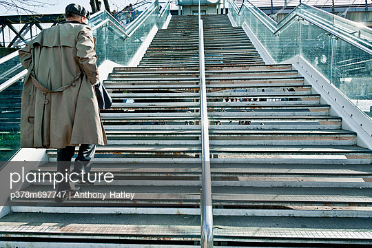 Rain coated man ascending steps - p378m697747 by Anthony Hatley