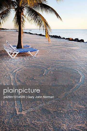Sun loungers beside heart shape on sandy beach, Islamorada, Florida Keys, USA