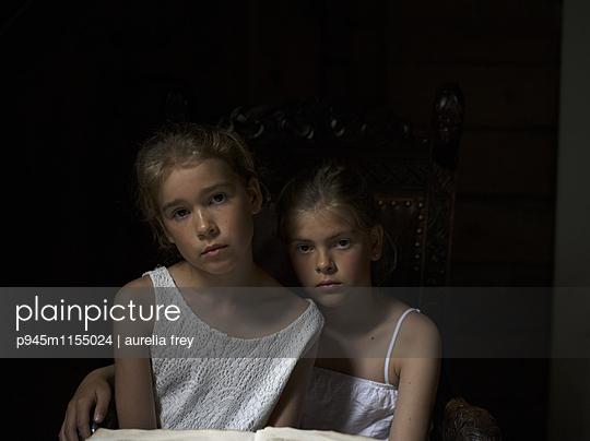 Zwei Mädchen sitzen vor einem Märchenbuch - p945m1155024 von aurelia frey
