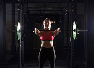 Portrait of determined female athlete lifting barbell in gym - p1166m1154114 by Cavan Images