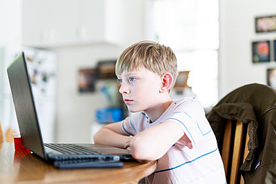 Teen watches educational video in kitchen during shelter in place - p1166m2191843 by Cavan Images