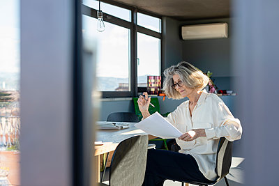 Senior woman checking paper while working at home - p300m2265871 by Emma Innocenti