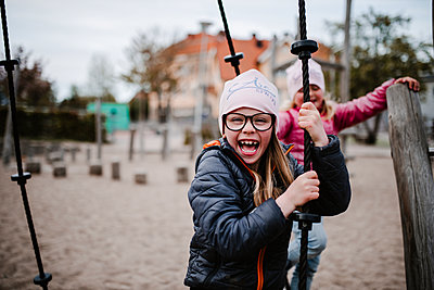 Happy girl on playground - p312m2208166 by Anna Johnsson